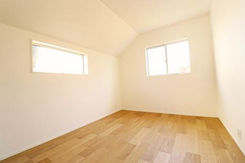 優しい色合いのフローリング張られた約5帖の洋室