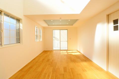 上部吹き抜けからの光が注ぐ、明るいリビングルーム