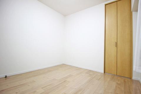 優しい色合いのフローリングが張られた約4.5帖の洋室