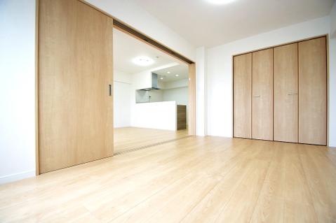 木目調で落ち着いた雰囲気のリビング横の約6.4帖の洋室