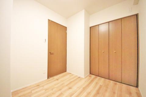 優しい色合いのフローリングが張られた約4.8帖の洋室